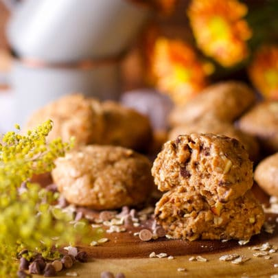 A stack of gluten free breakfast cookies on a wood tray with fresh flowers and coffee mugs in the background.