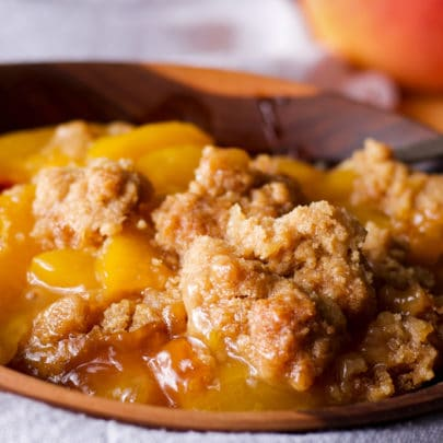 A bowl filled with warm peach cobbler.