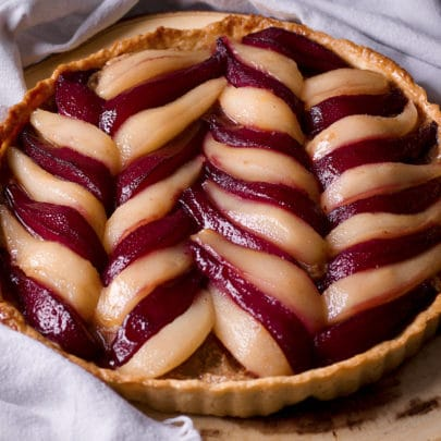 A pear tart with red and white wine poached pears set in a decorative pattern over frangipane filling.