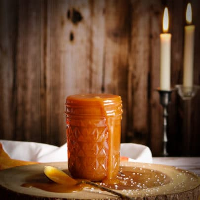 A jar of salted caramel sauce with caramel sauce dripping down the side of the jar and a spoon laying on the same surface as the jar with caramel sauce spilling from it.