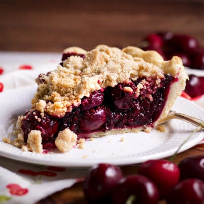 A slice of Cherry Crumb Pie on a white plate with fresh cherries scattered on the table all around the plate.