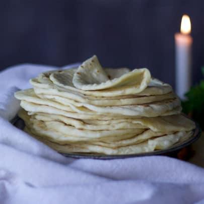 A stack of soft, warm homemade flour tortillas.