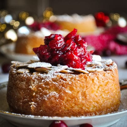 A mini almond cake topped with cranberry sauce on a small white plate with other mini cakes in the background.