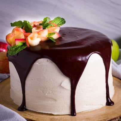 A frosted layer cake topped with chocolate ganache and decorated with apple roses.