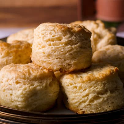 Warm, flaky homemade buttermilk biscuits stack on a plate, ready to eat.
