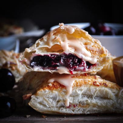 A stack of two cherry turnovers with the top turnover broken in half so you can see the cherry cream cheese filling.