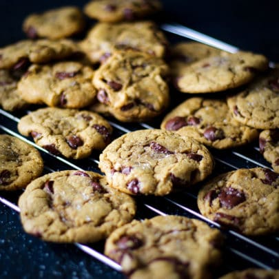 A baking rack piled with freshly baked chocolate chip cookies.