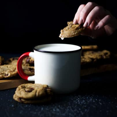Someone dipping a chocolate chip cookie in a mug that's filled with milk. The mug is surrounded by stacks of chocolate chip cookies.