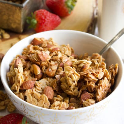 A bowl filled with homemade granola, with milk and fresh strawberries in the background.