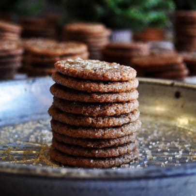 A stack of mini gingersnap cookies on a tin plate with more stacks of mini cookies in the background.