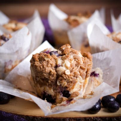 Blueberry muffins on a wood tray with the center muffin