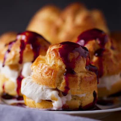 A tray of ice cream filled profiteroles that have been drizzled with red wine dessert sauce.