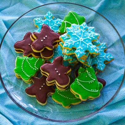 A glass plate piled with decorated Christmas cookies in the shape of gingerbread men, Christmas trees, and snowflakes.
