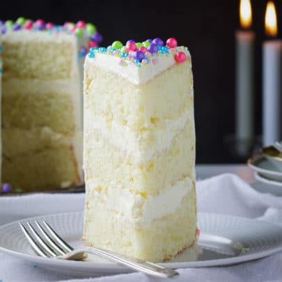 A slice of Buttercream Frosted Vanilla Layer Cake on a plate with a fork.