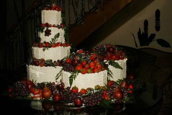 A multi tiered wedding cake made of cheesecake and topped with fresh fruit.