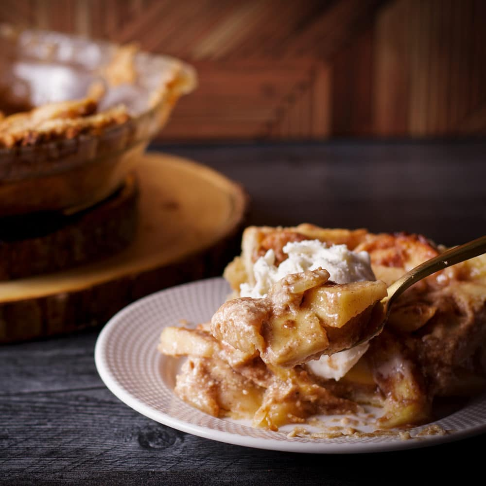 Someone using a fork to lift a bite of German Apple Pie from a slice.