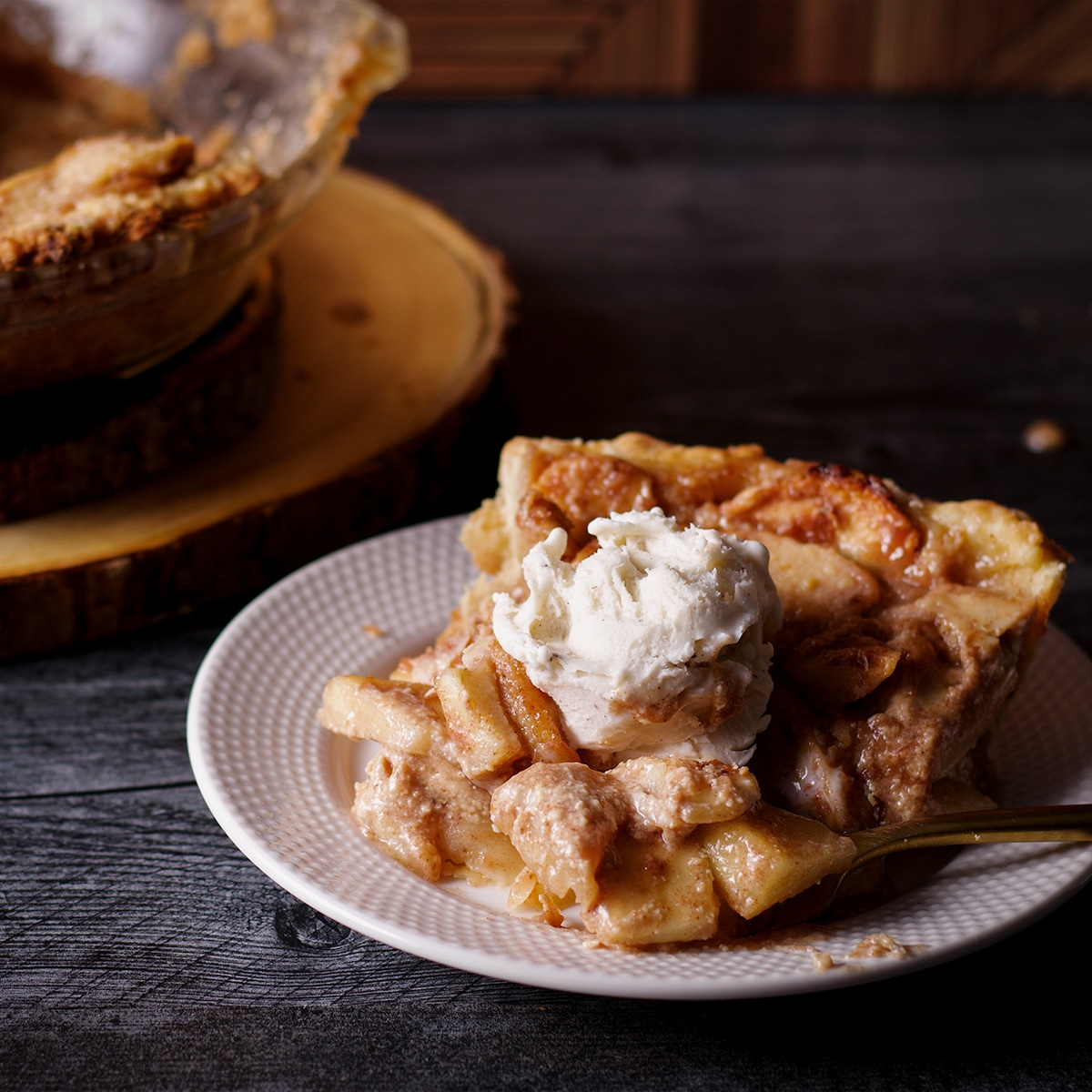 A slice of German Apple Pie topped with a scoop of vanilla ice cream.