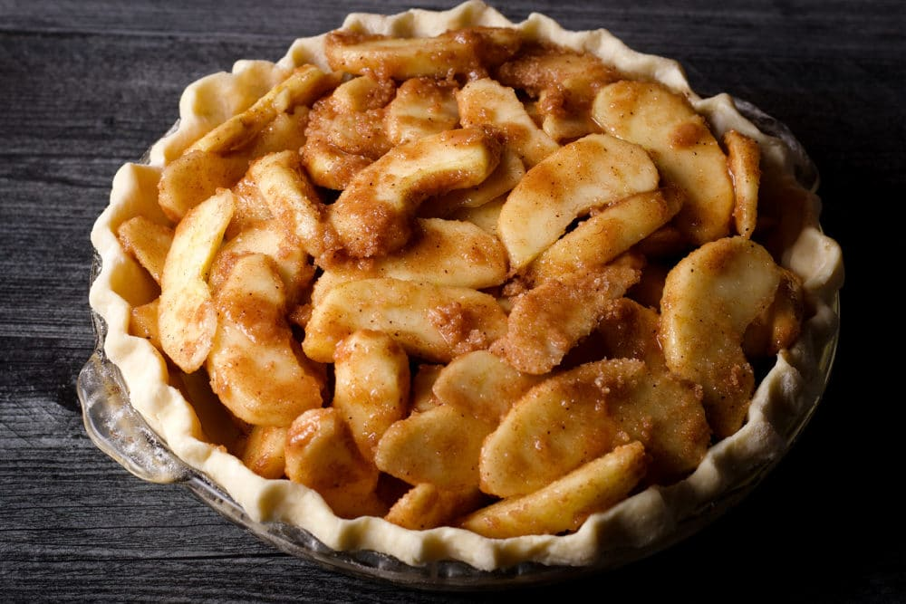 Sliced apples coated in cinnamon and sugar piled inside a pie crust.