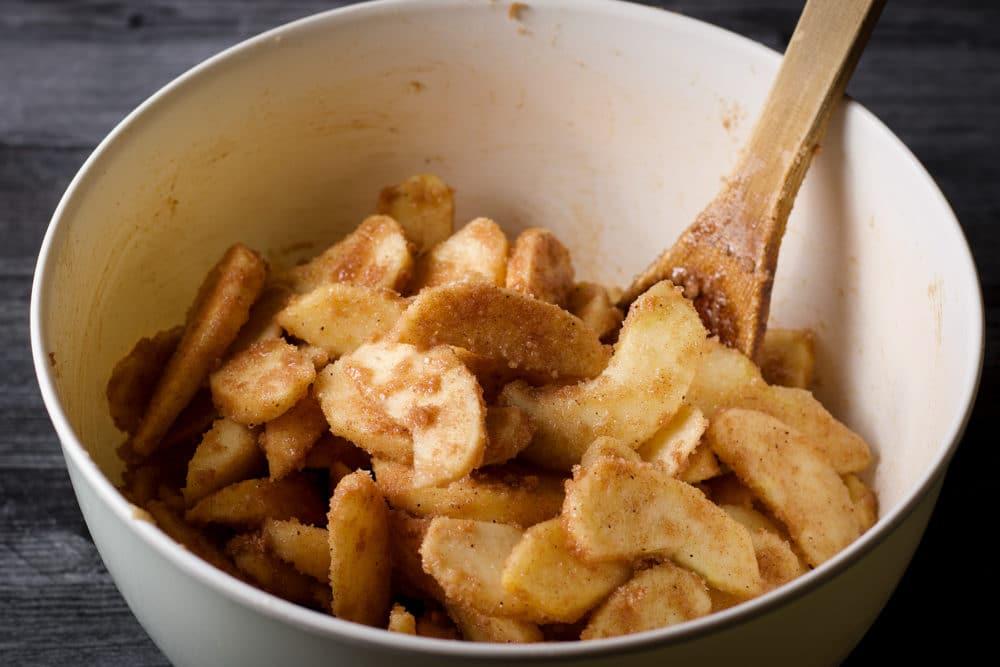 Stirring apples with cinnamon and sugar to make German Apple Pie