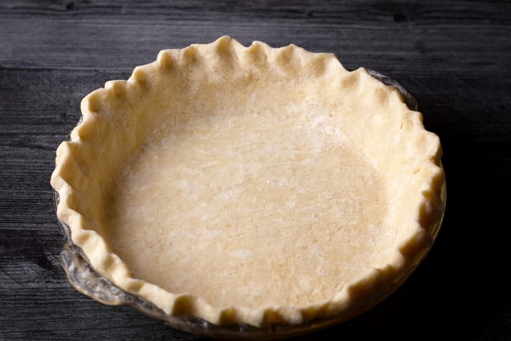 A pie plate that's been fitted with a bottom pie crust.