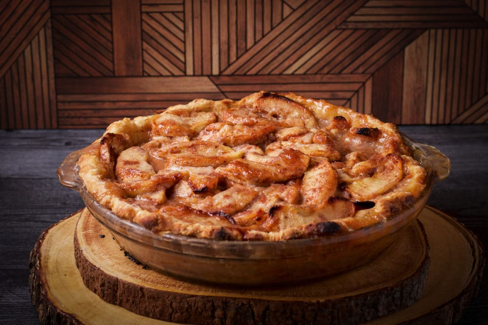 A whole, freshly baked German Apple Pie on a wood board, ready to slice and serve.