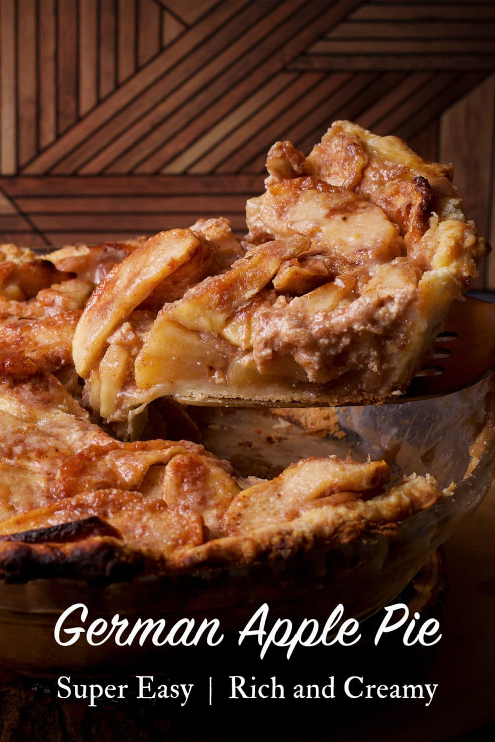 Using a spatula to lift a slice of German apple pie from the whole pie.